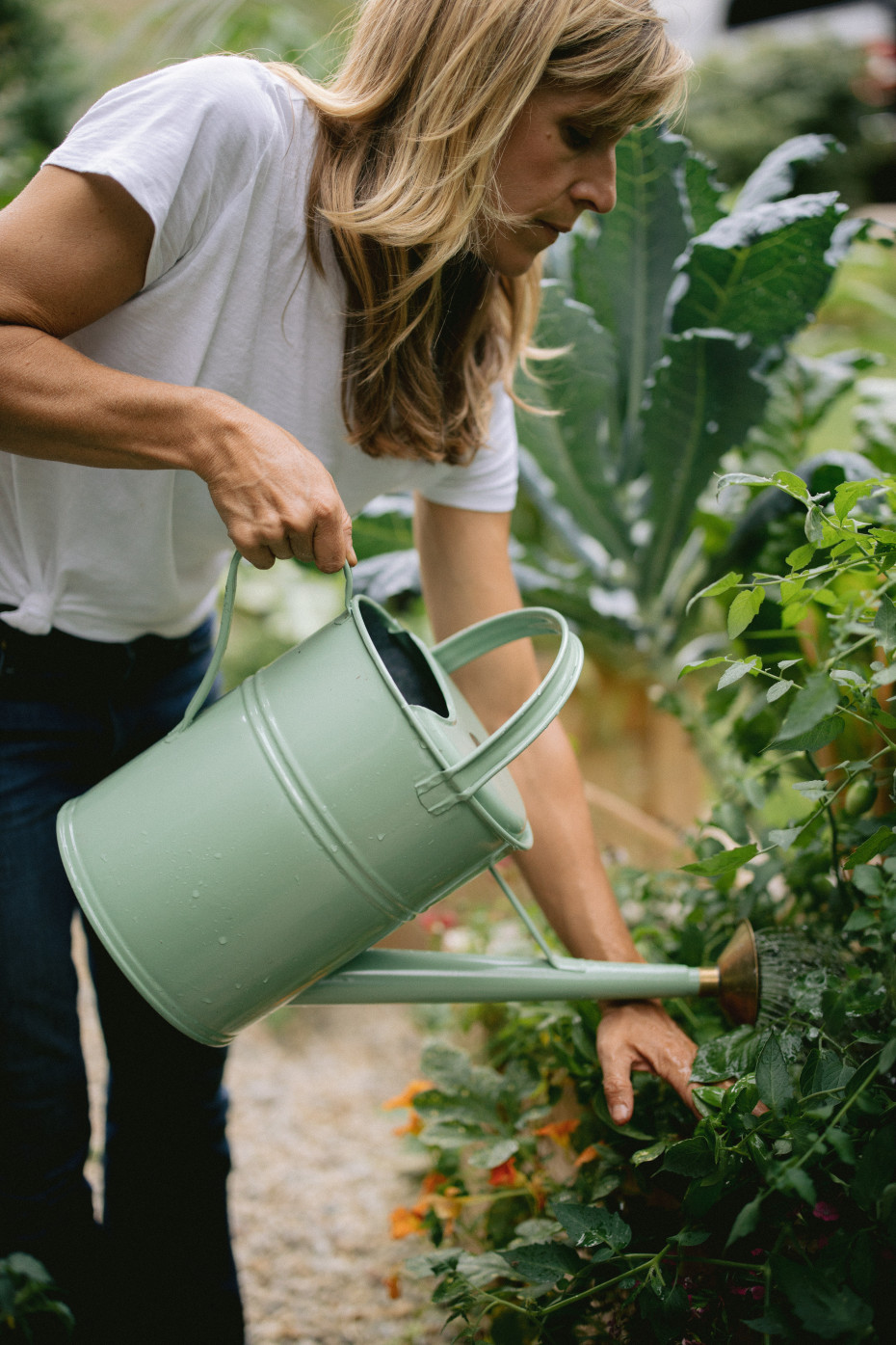 Nicole Burke of Rooted Garden, GardenaryCo, Gardenary.Com watering some plants with a mint green vintage watering can